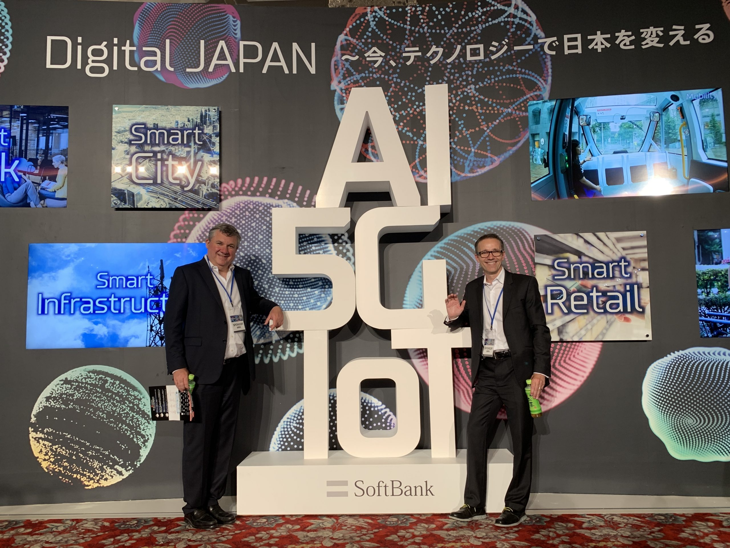 Blaine and Miguel of VANTIQ pose in front of SoftBank sign