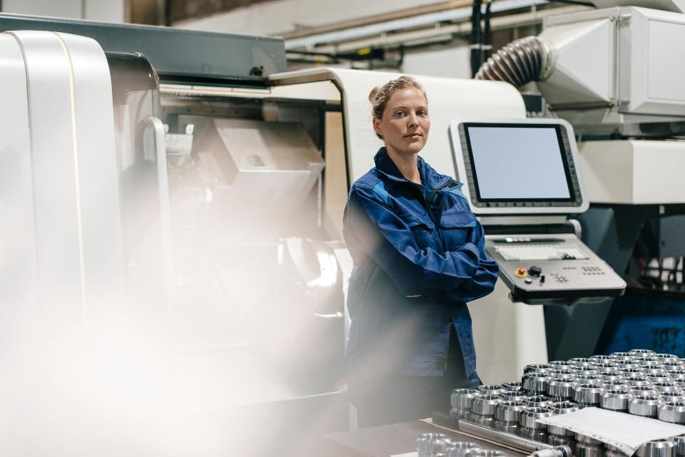 a female factory worker standing in front of machinery
