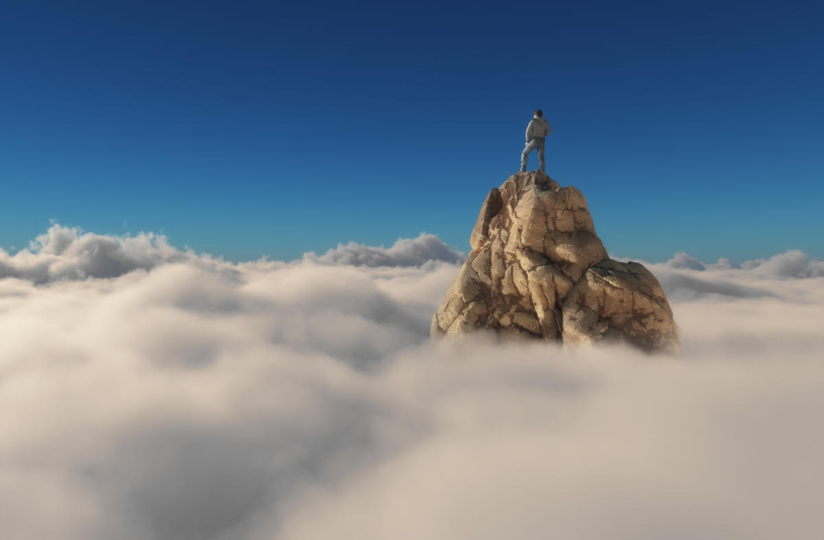 person standing on top of mountain above clouds