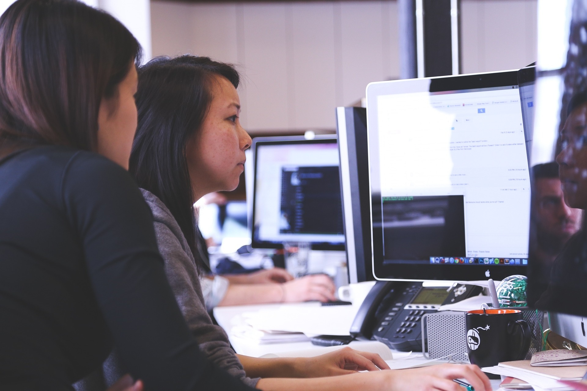 two female employees working in front of the computer in the office